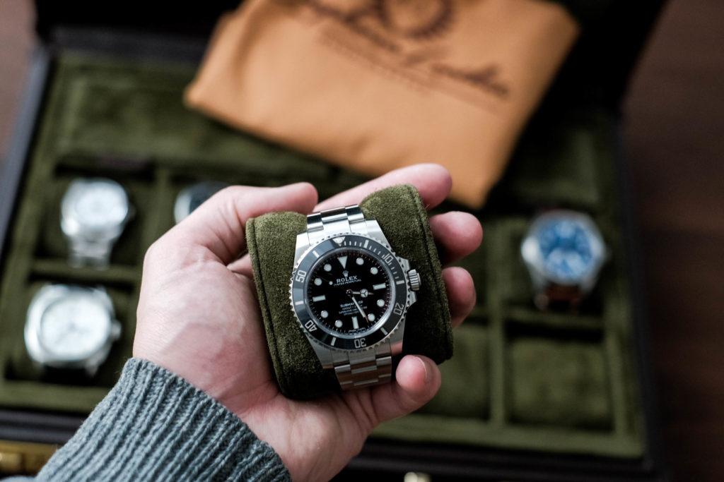 Rolex submariner in hand with case in background