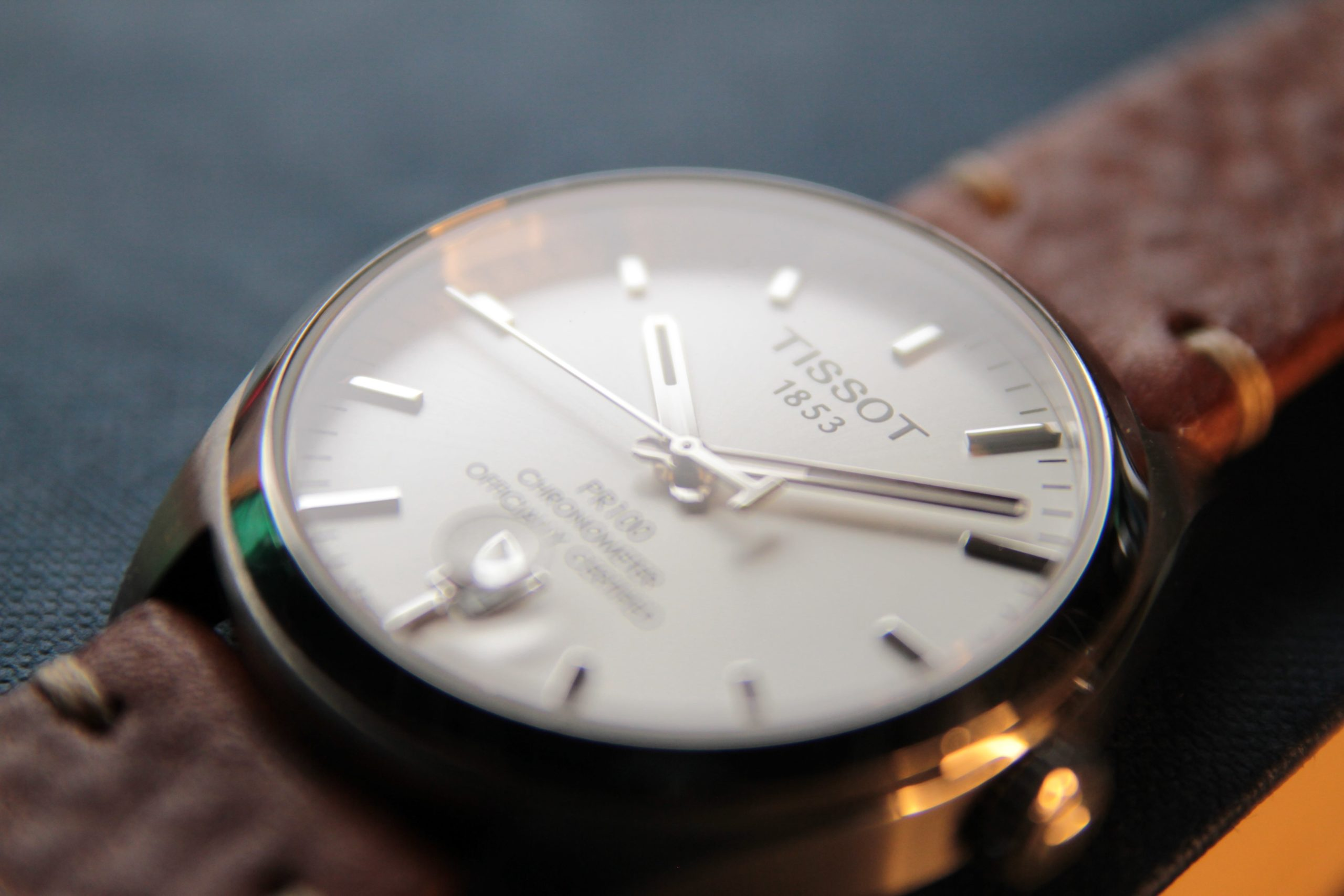 Close up of crystal, case, and Tissot logo